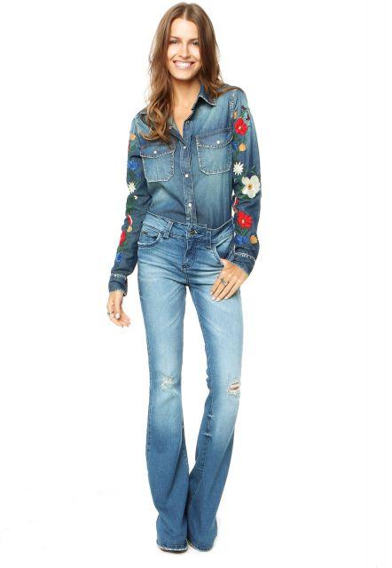 Modelo usa calça jeans flare, camisa jeans lavagem desbotada com flores bordadas na manga.