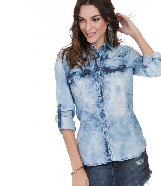 Modelo usa saia jeans escura, camisa jeans clara meia manga.