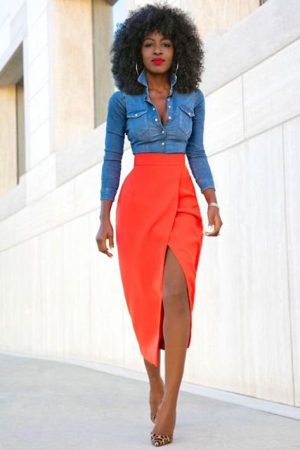Modelo usa saia laranja midi com fenda, camisa jeans coladinha e sandalia.