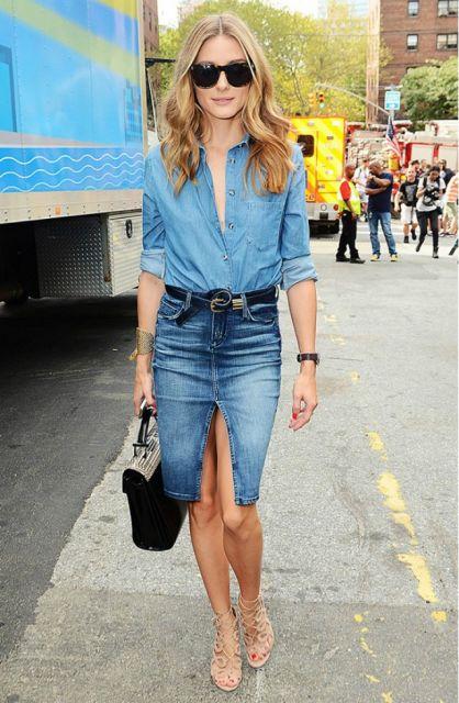 Modelo usa saia jeans azul com fenda, camisa jeans azul clara e sandália nude.