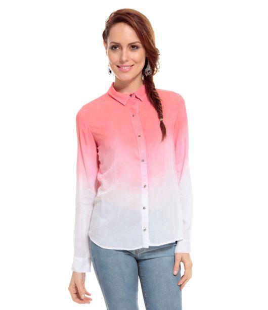 Modelo usa camisa tie dye branco com rosa e calça jeans.