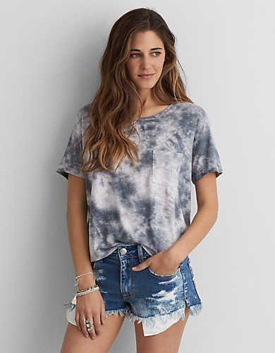 Modelo usa short jeans, camiseta tie dye cinza.