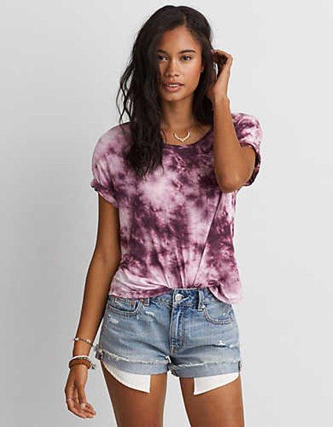 Modelo usa short jeans e blusa cor de rosa tie dye.
