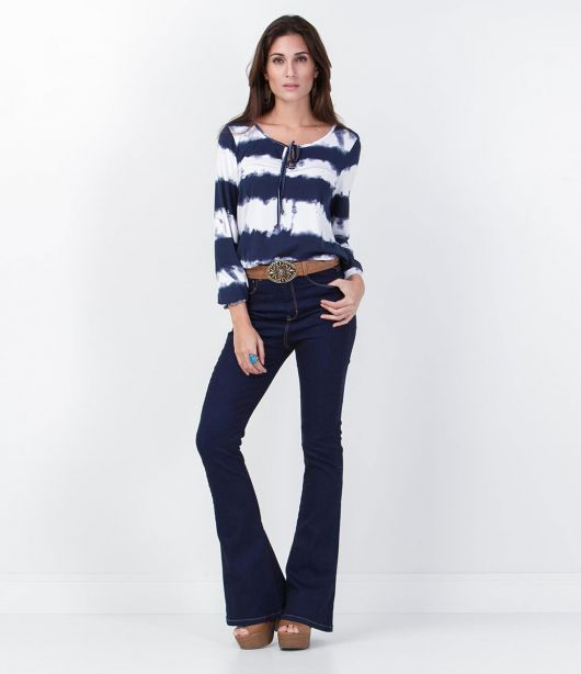 Modelo usa blusa tie dye azul e branco com calça flare azul jeans.