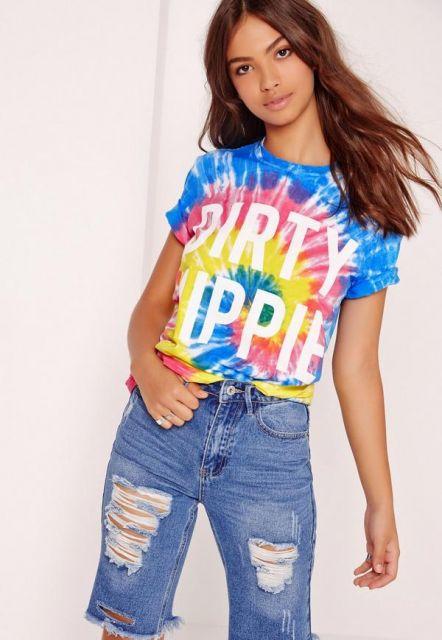 Modelo usa calça jeans destruída, camiseta colorida tie dye, azul, amarelo e rosa.