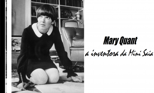 Mary Quant criadora da mini saia sentada no chão com vestido curto preto de gola branca.