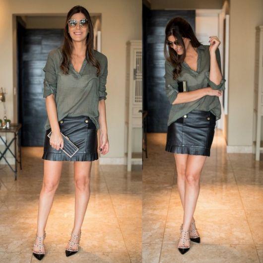Modelo usa saia preta com blusa verde musgo e sapato preto de bico fino e spikes.