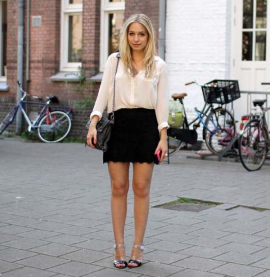 Modelo veste saia preta, camisa branca social e sandalia cinza.