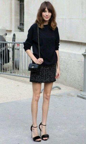 Modelo veste saia preta, blusa manga longa preta e sandalia preta com bolsinha clutch preta.