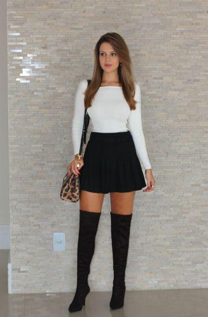 Modelo usa blusa branca manga longa, saia preta e bota de cano alto preta.