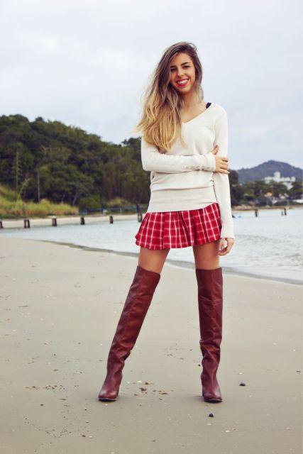 Modelo veste saia vermelha xadrez e bota cano longo vermelha.