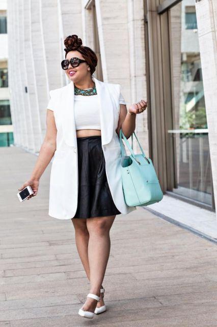 Modelo usa saia preta com blusa branca cropped, colete e sapato na mesma cor e bolsa azul claro.