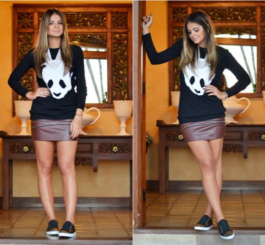 Modelo usa saia marrom de couro com moletom preto estampado de branco e tenis marrom.