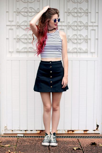 Modelo usa saia preta de botoes com blusa listrada cropped e tenis.