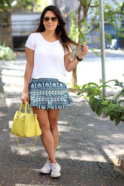 Modelo usa tenis branco, saia estampda azul e blusa branca.