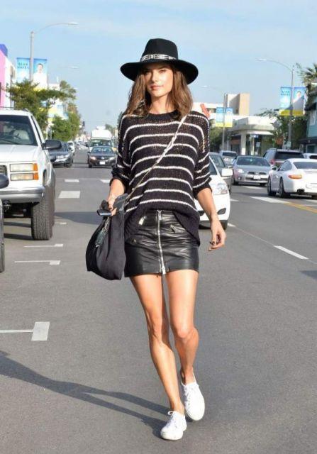Modelo veste saia de couro preta curta com blusa preta e branca listrada, bolsa transversal preta, tenis branco e chapéu feminino preto.