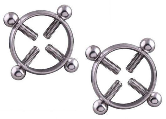 Dois piercings de mamilo, com argola e quatro pinos cada.