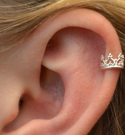 Piercing em formato de coroa.