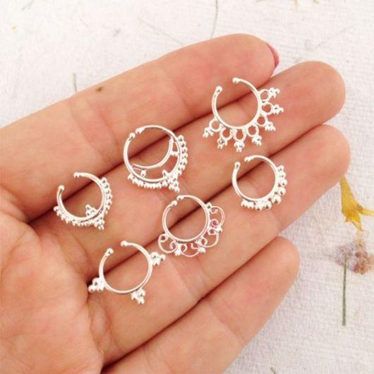 Pessoa segurando seis piercings diferentes.