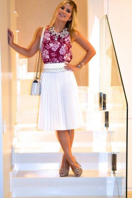 Modelo usa saia branca plissada, blusa estampada em vermelho, sandalia e bolsa.