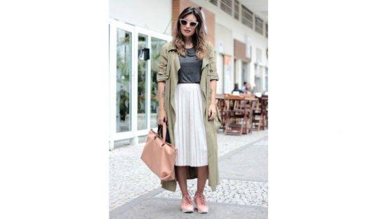 Modelo usa saia branca plissada, casaco verde longo, tenis e bolsa rosa nude e blusa azul marinho.