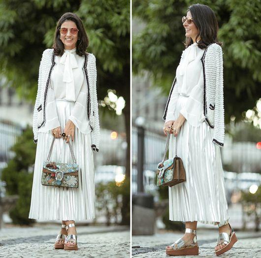 Modelo usa sandalia verniz prata, bolsa verde de mão, saia branca plissada e blusa branca com casaco cinza.