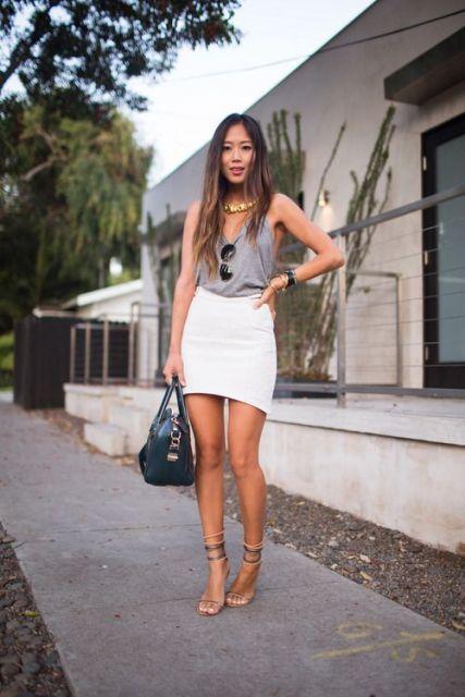 Modelo usa saia branca curta justa com blusa cinza de alcinha e sandalia tiras finas.