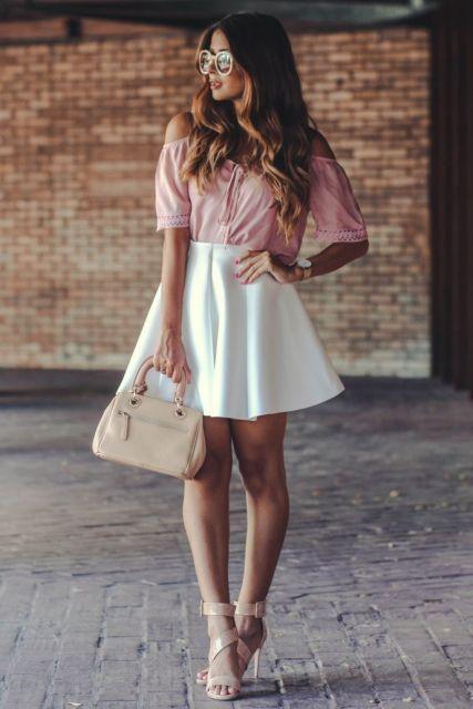 Modelo usa blusa rosa de babados, saia branca, bolsa bege e sandalia nude.