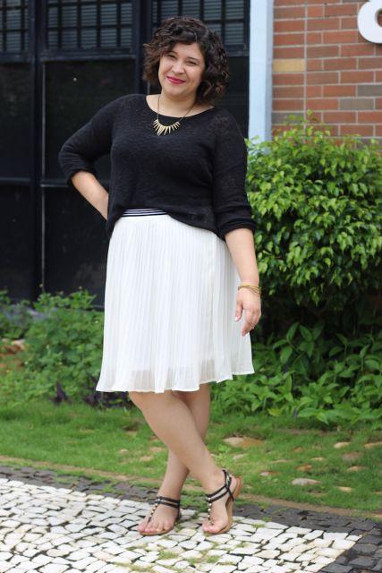 Modelo veste saia branca comprimento midi, blusa preta e sandalia .