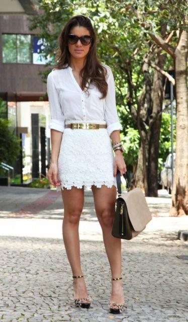 Modelo usa saia branca curta e camisa branca com sandalia de salto e bolsa na cor marrom.