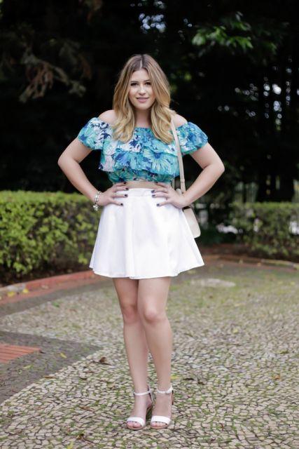 Modelo usa cropped azul, saia branca e sandália na mesma cor.
