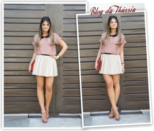 Modelo usa saia branca, blusa nude rosê com estampa de bolinhas brancas e sandalia na mesma cor.