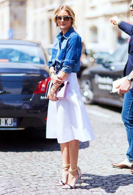 Modelo usa saia midi branca rodada, com camisa jeans, clutch rosê e sandalia.