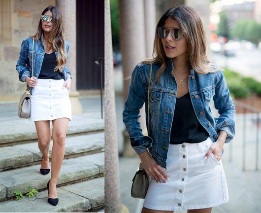 Modelo usa saia branca de botões, com blusinha preta, camisa jeans e sapatilha preta.