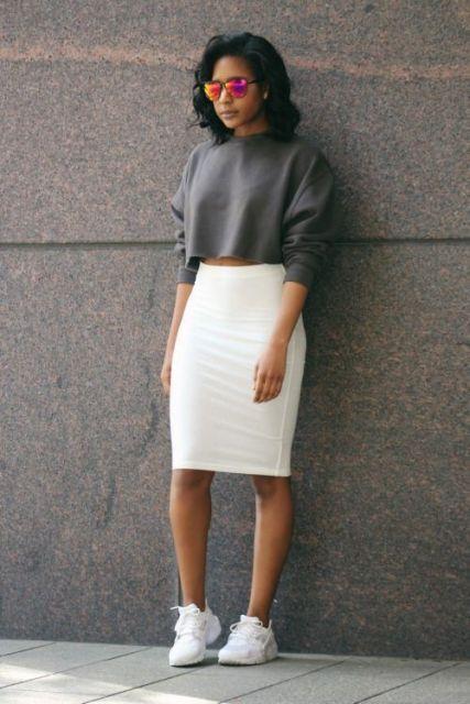 Modelo usa saia branca, moletom cinza chumbo e tenis branco.