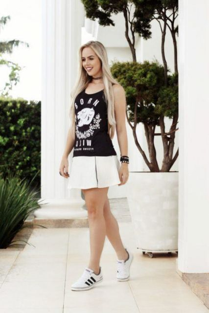 Modelp usa saia branca, regata estampada preta e tenis preto com branco.