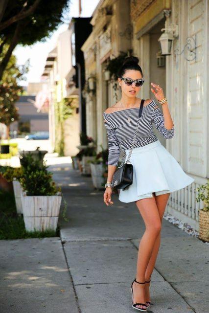Modelo usa saia branca, blusa listradaombro a ombro com sandalia e bolsa.