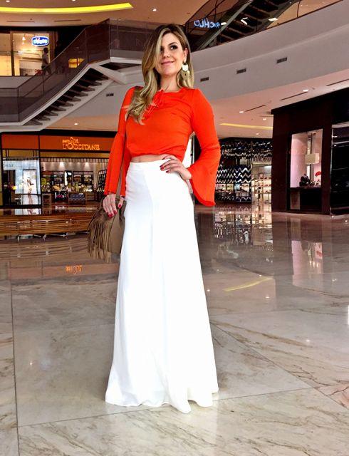 Modelo usa saia branca longa e blusa cropped laranja manga longa.
