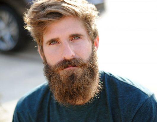 Homem de olhos muito claros olhando para a câmera com uma barba meio ruiva e grande.