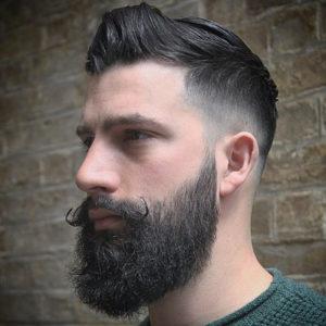 Homem de perfil com um cabelo cortado com undercut e uma barba cheia com o bigode levemente recurvado para cima.