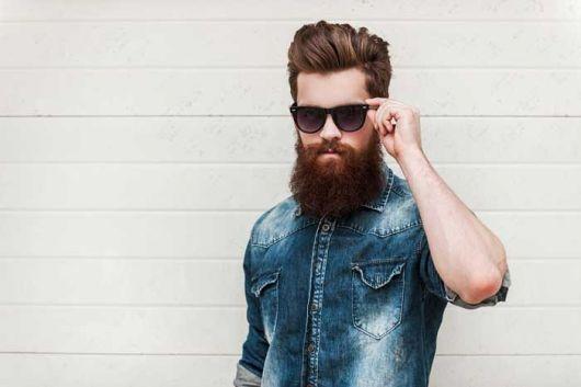 Homem de jaqueta jeans e óculos escuros com uma barba bem cheia e cabelo penteado para trás.