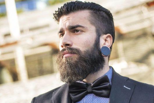 Homem visto de baixo para cima com uma gravata borboleta, cabelo em corte undercut, alargador grande preto e uma barba cheia e bem aparada.