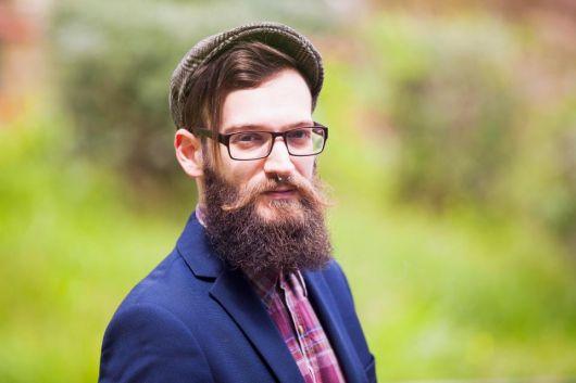 Homem de roupa social, boina, óculos de grau e uma barba grande e volumosa.