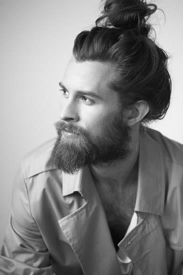 Homem de perfil com um cabelo grande preso por um coque e uma barba média e volumosa.