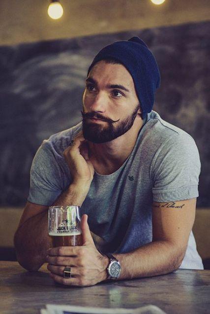 Homem com uma cerveja recostado em um balcão vestindo uma touca. Sua barba é rala nas laterais e maior no cavanhaque e bigode, levemente recurvado para cima.