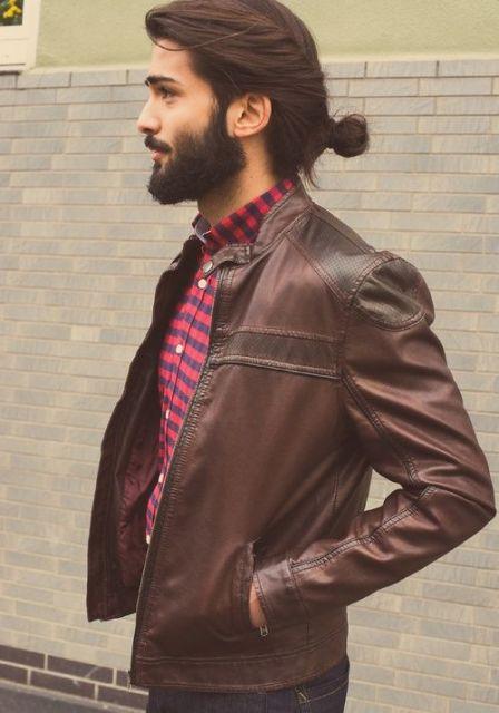 Homem de perfil usando uma jaqueta jeans, barba bem feita e um coque.