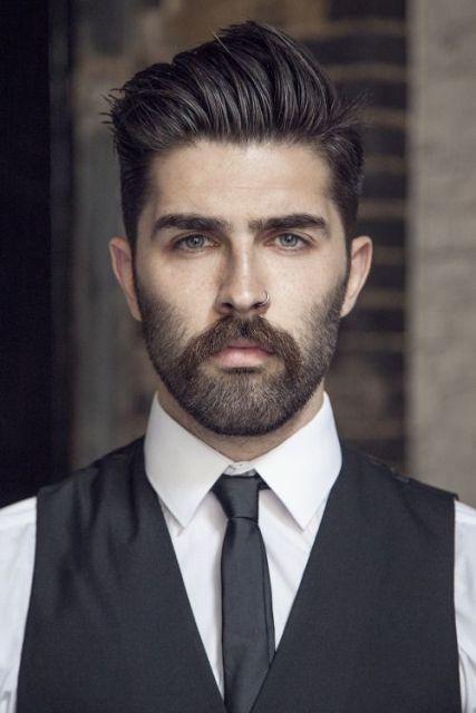 Homem com roupa social, cabelo penteado com muito gel para o lado e uma barba rala nas laterais, mais cheia no bigode.