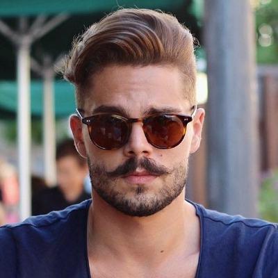 Homem de óculos escuro com cabelo bem penteado para o lado e uma barba rala mais cheia no bigode.