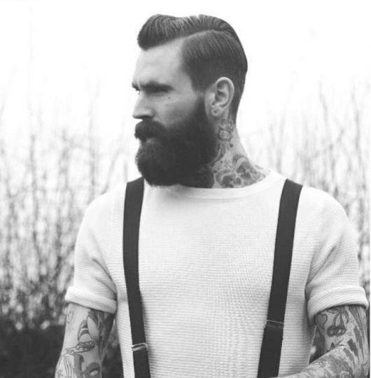 Homem de perfil com muitas tatuagens e um suspensório com barba hipster bem cheia e um cabelo bem penteado.