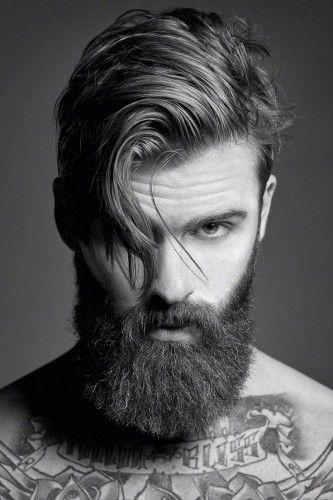 Rosto de um homem com barba grande e cabelo grande jogado para o lado, cobrindo parte do olho.